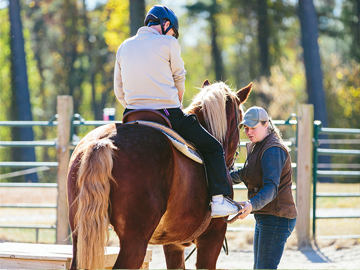 A guest prepares to enjoy a trail ride on horseback as a Biltmore employee assists
