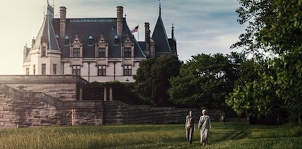 two people walking in gardens with view of biltmore house