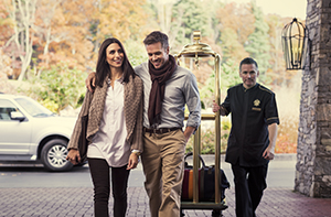 man and woman in fall clothing walking into Inn with a bellhop pulling a luggage cart and colorful fall trees behind them