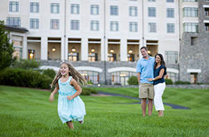 young child runs across lawn of The Inn while parents look on