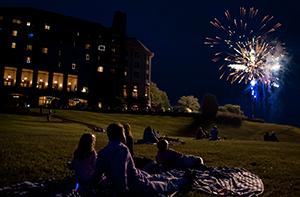 Fireworks watched by people on blankets in front of The Inn