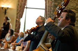 men playing stringed instruments in the Library Lounge of the Inn as people mingle in the background
