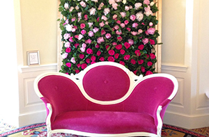 Mother's Day photo station with Victorian-style couch and backdrop of ombre flowers