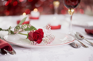 roses on a table with red wine