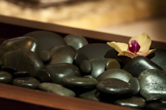 Smooth black stones in a wooden bowl