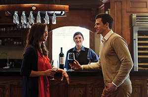 A man and woman standing at a counter in the winery tasting wines