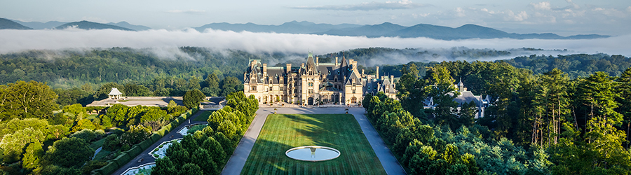 Biltmore house seen from a distance with clouds floating across the Blue Ridge Mountains in the background