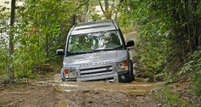 a land rover vehicle drives on a bumpy muddy road