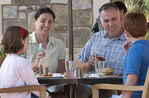 family with young children dining in an estate restaurant outside on a patio