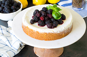 cheesecake on a cake stand topped with berries and basil, with lemons and berries in the background