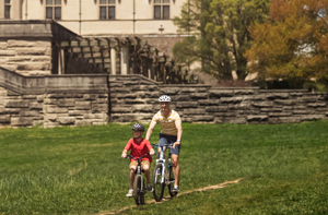 adult and child ride bikes on bike trails near biltmore house