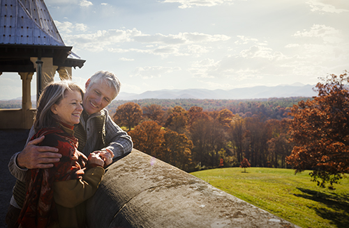 man and woman stand on rooftop of biltmore house admiring the fall view