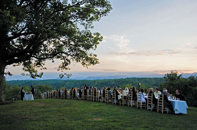 A Moveable Feast with tables lined end to end and people enjoying harvest-fresh foods with a great view
