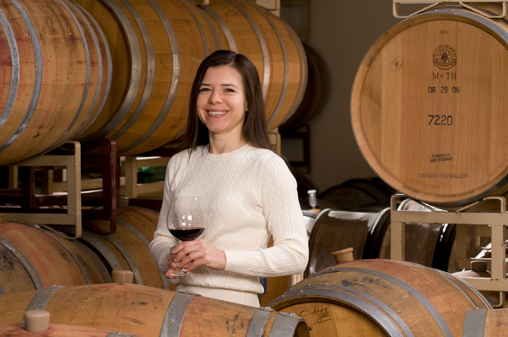 Sharon Fenchak standing in front of wine barrels