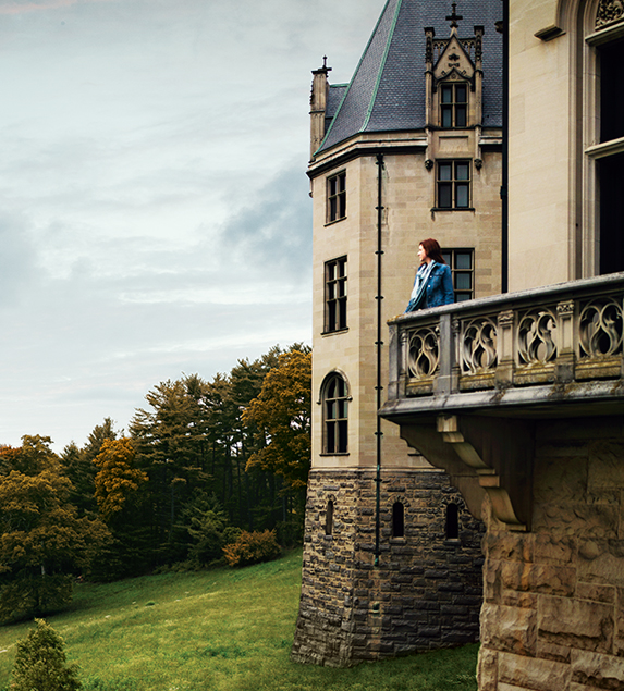 a person enjoying the view of the estate from a balcony on biltmore house