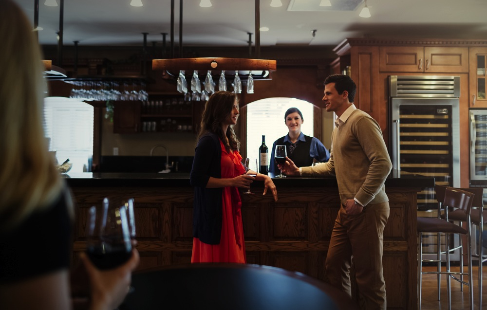 two people drinking wine by a bar