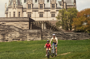 adult and kid ride bikes past biltmore house