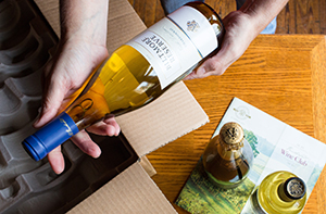 hands holding a bottle of biltmore wine just unpacked from a delivery box