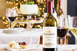 Bottle of Cabernet Sauvignon on a holiday table with white lights sparkling in the background and desserts visible