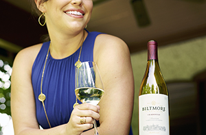 woman holding glass of Biltmore Estate Chardonnay at an outdoor gathering