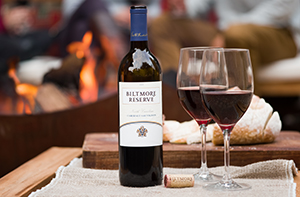 Bottle of biltmore red wine sitting on some folded burlap outside with a firepit and people in the background