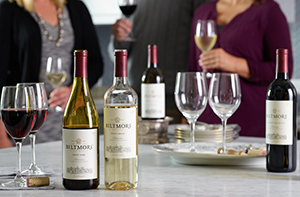 bottles of biltmore wine and glasses on a kitchen island with people mingling in background