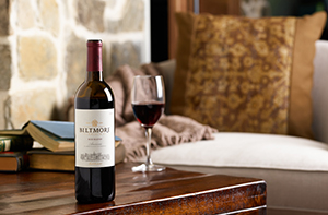 bottle of red wine and glass on wood table with cozy chair next to stone edge of fireplace in background