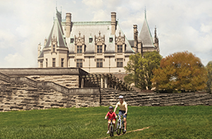 child and adult on bicycles on a bike trail going past Biltmore House on a sunny summer day