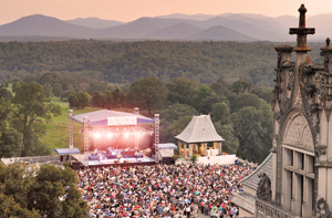 Hazy, slightly pink sky with mountains in back ground.  In the foreground, the Biltmore Mansion is on the right and the lelft is the tent for concert artist at Biltmore Summer Concert Series.  Concert goers are pictured in front of the tent stage.