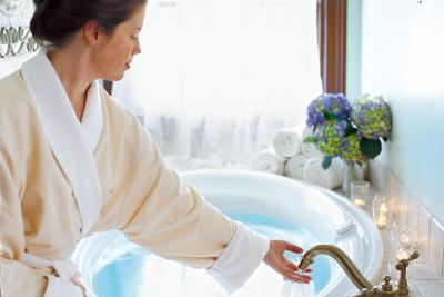 woman in robe drawing a bath