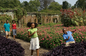 family of four in the walled garden surrounded by flowers