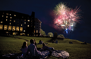 fireworks over antler hill village with people lounging on blankets watching