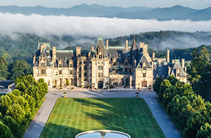 summer image of biltmore house surrounded by bright blue sky and green foliage