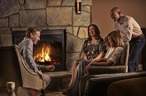 people gathered around a fireplace in Village Hotel in comfortable chairs, chatting