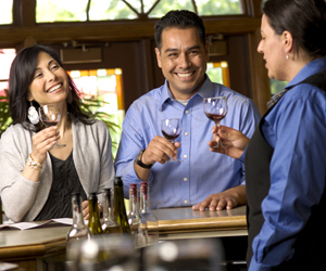 Couple talking to Winery tasting employee with glasses of red wine