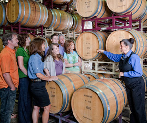 Group of people listening to tour guide in room full of stacked wine barrels