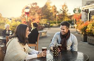 two people enjoying warm beverage sitting outdoors in Antler Hill Village