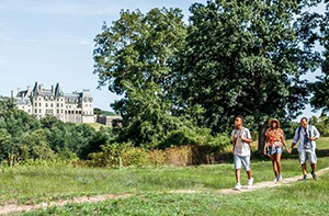 A family taking a casual hike on estate grounds with trees and Biltmore House in the background