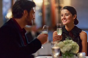 two people dining and toasting with bubbly