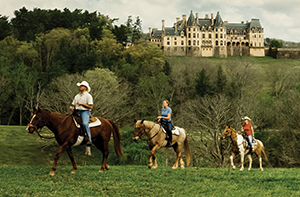 Three people on horseback wind their way across lush estate grounds with Biltmore House on a hill in the background