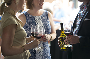 People mingling and chatting at a wine release event at Biltmore with glasses of wine in their hands