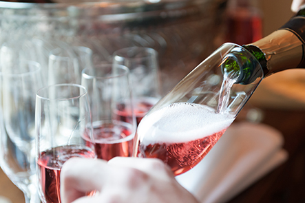 closeup of pink sparkling wine being poured into glass flute