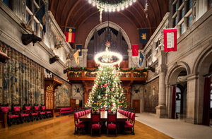 Biltmore's Banquet Hall decorated with a huge fir tree covered in lights and ornaments lit from above by a large chandelier.