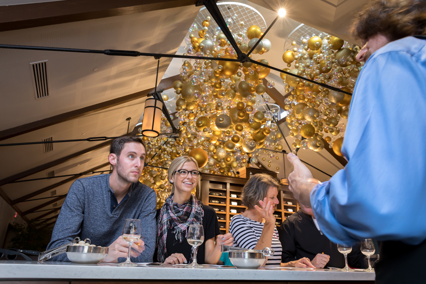 Couple interacting with wine host with decorations in background.