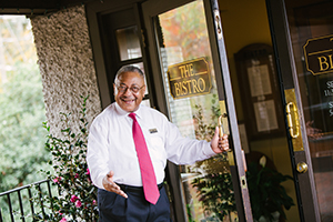 Biltmore employee welcoming customers to The Bistro restaurant and extending Gracious Hospitality to them.