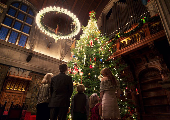 A family admires the Banquet Hall Christmas tree during Candlelight Christmas Evenings