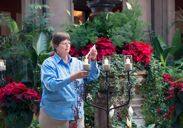 A Floral team member lights candles at Biltmore