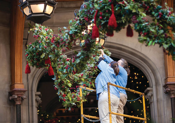 Floral team members hang kissing balls as decorations
