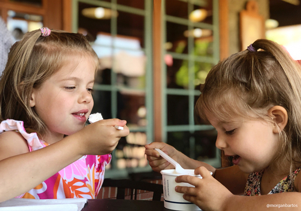 Two young girls enjoy ice cream