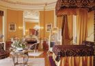 <b>Mrs. Vanderbilt's Bedroom</b> is a feminine retreat decorated with purple and gold silk fabrics and furnished in the Louis XV style. This oval room has a richly painted ceiling and doors that lead to the Lady's Maid's Room, the bathroom, and closets.